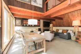 Living Area - Includes dining table, sofa bed, heated floor, and a wood burning fireplace.