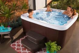 7-person hot tub on covered porch with additional 4-person tub in yard (stock image used)