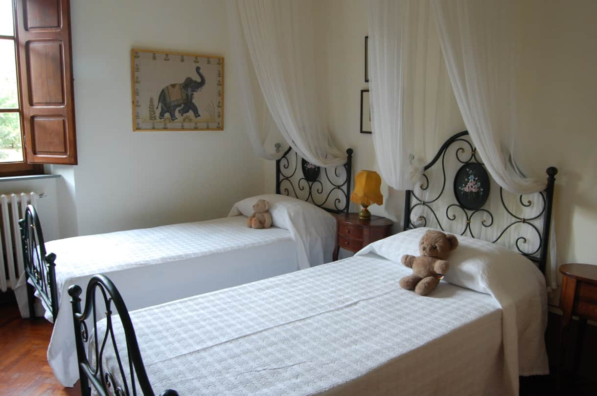 Bedroom 5 of this Tuscan villa has views to Cortona and an en suite .