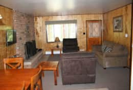 cabin 3 dining room living room brick fireplace smart TV and sleeper sofa