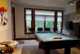 Game room in basement with TV, pool table and ping pong table