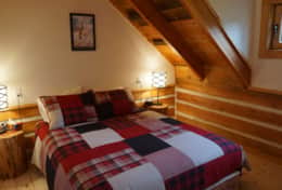 A cozy queen bed in one of the upstairs bedrooms