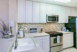 High-end appliances, under-cabinet lights, tile backsplash and Corian countertop