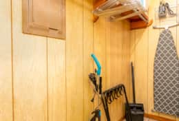 Closet with essentials; luggage rack, vacuum cleaner, broom/duster, iron/board