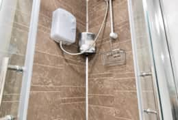 Shower cubicle with eco-power sower and toiletries in place