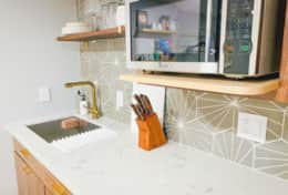 Kitchenette with Microwave, Mini Refrigerator, Plates, Cups and Silverware.