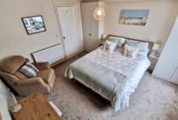 Large, kingsize bed with seating area and storage