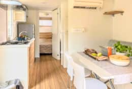 large daytime area with a kitchenette, table, chairs, refrigerator with freezer, sink, dishes, pots,