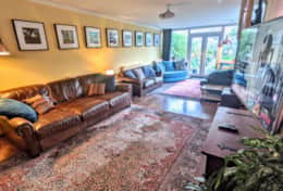 Living room full of comfy sofas, wood burning stove, 55
