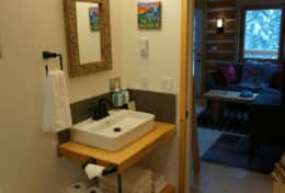 Bathroom has composting toilet, natural timberwork vanity, local hand cut slate and local artwork