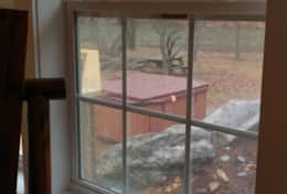 view from windows of sunroom to hot tub, fire pit, river