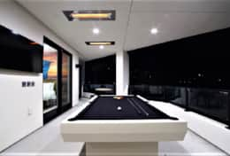 Pool table at night with in-ceiling heaters