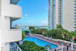 View of fully furnished balcony of downtown Miami and Biscayne Bay, and pool