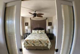 Bedroom with a/c, lanai access and pocket doors with privacy curtains.