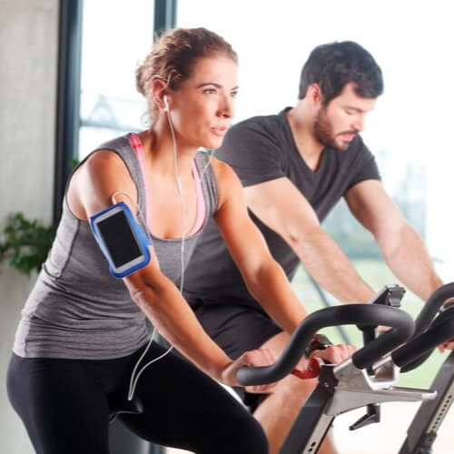 Couple Riding Stationary Bikes in Fitness Center at Quintessential Quarters