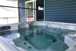 Six person hot tub is located on screened porch.