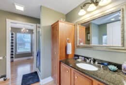 Master en-suite bathroom with shower, soaking tub, and granite countertops