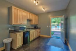 Lower level kitchenette has heated, sealed concrete floors with direct access to the hot tub + pool