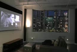 Living room area has a projector TV, daybed (can sleep 1).