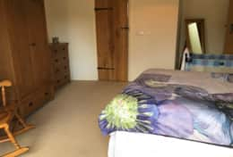 Master bedroom has ensuite shower room, large wardrobe, chest of drawers, rocking chair and bedside