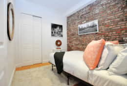 Decorated with colorful pillows to contrast the brick walls.