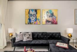 Soft plush black sectional combined with great modern paintings.