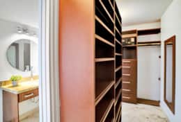 Master bedroom walk in closet with safe, view of vanity in bedroom also