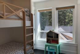 Bunk room with forest view includes toys, doll house, and children's books.