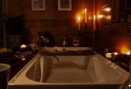 Unwind and soak in the deep bath with candles and bubbles