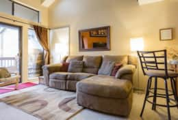 Comfortable living room with reclining couch and ski run views of Park City Mountain Resort