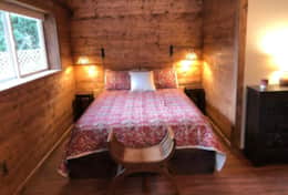The Barn Cottage has a open floor plan. The sleeping area features a king size bed.