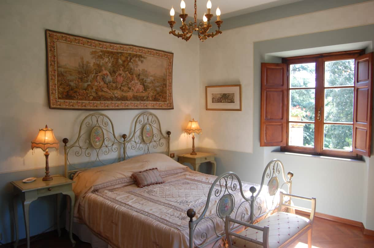 Bedroom 1 of this Tuscan villa with 2 windows and views over the pool, the olive grove and beyond