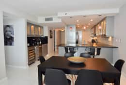 Dining area with seating for 6 at table and 2 at kitchen counter, wet bar, fully equipped kitchen